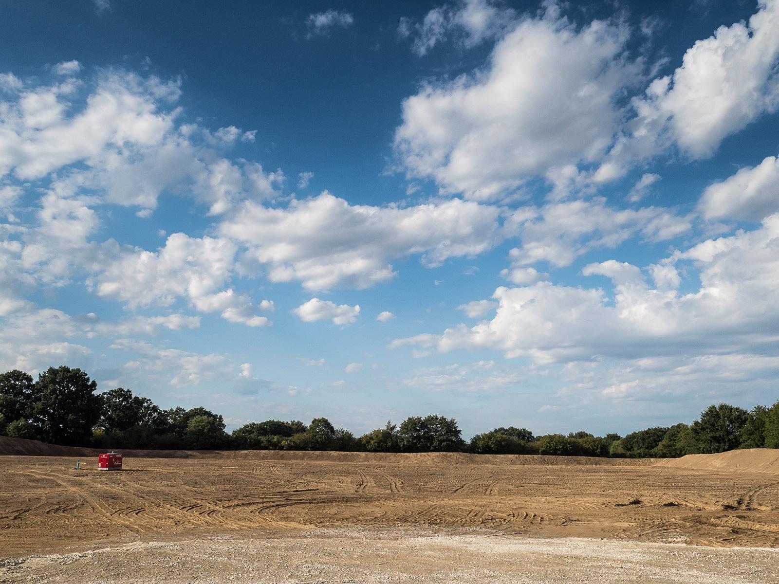 Planiertes ehemaliges Getreidefeld mit rotem Container und dekorativen norddeutschen Wolken drüber