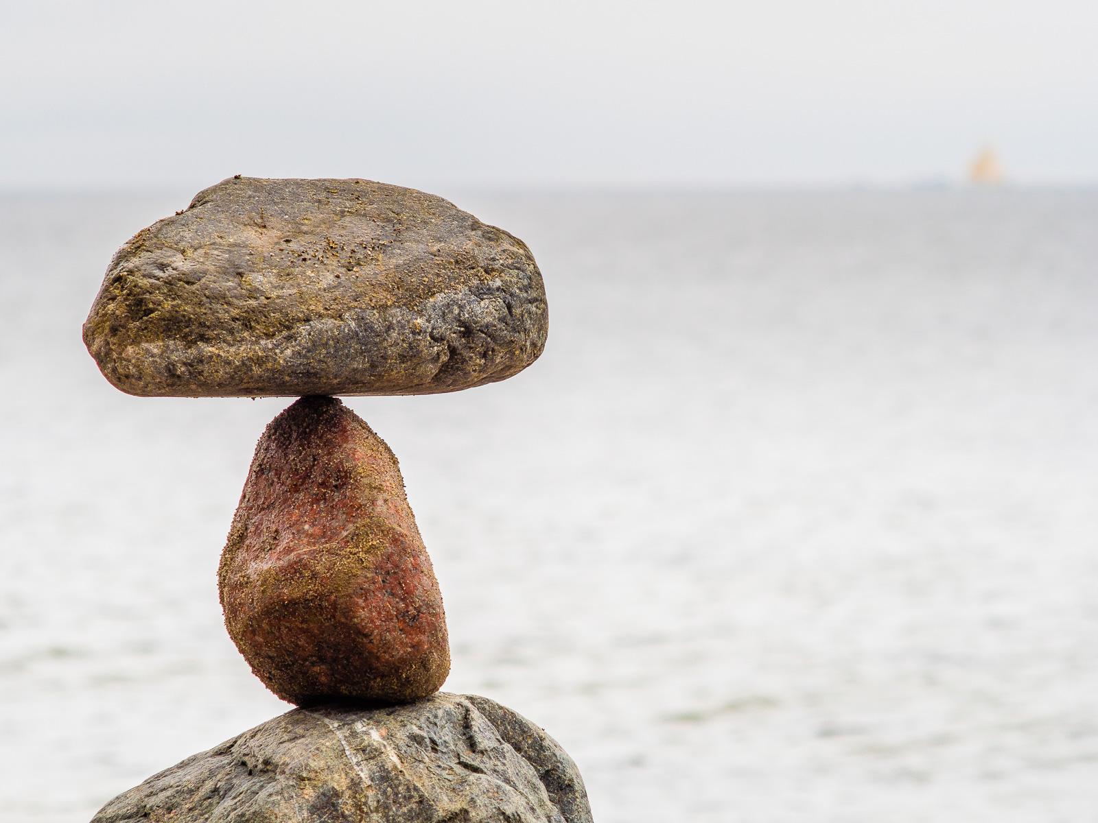 Steinpyramide vor unscharfem Segelboot