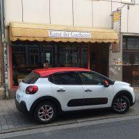 Kleinwagen mit lustig-modernem Design vor Antiquitätengeschäft