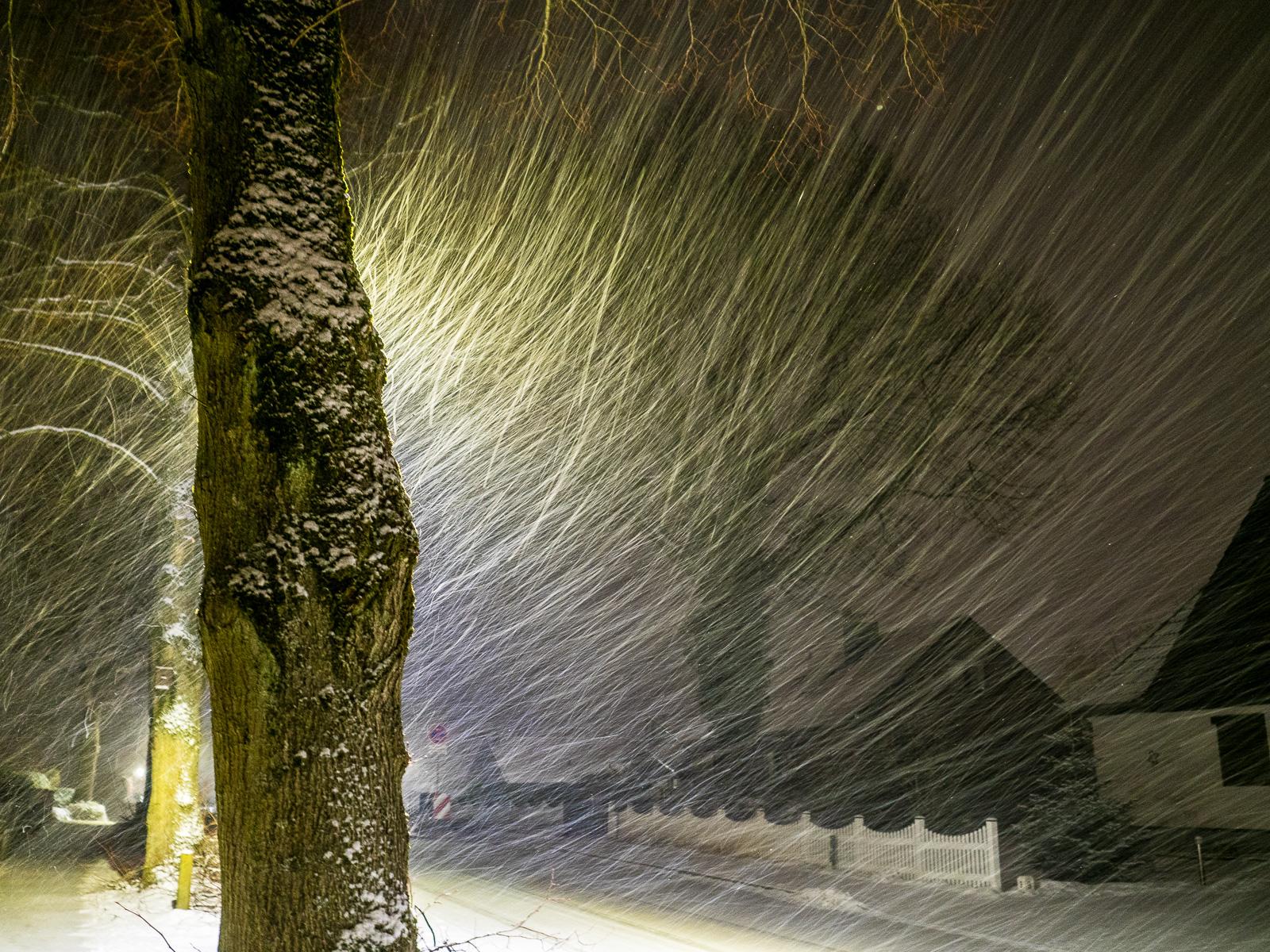 Schneegestöber im Dorf bei Nacht